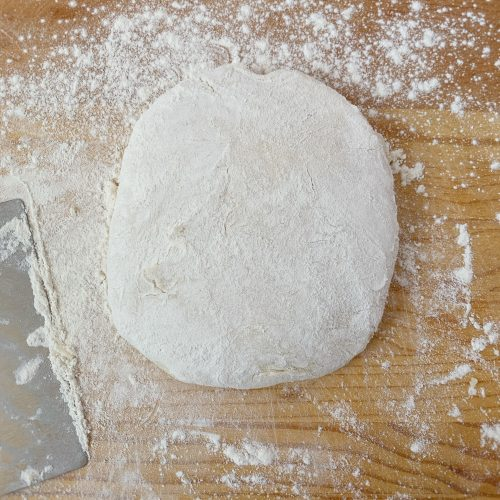 Ball of pizza dough on cutting board