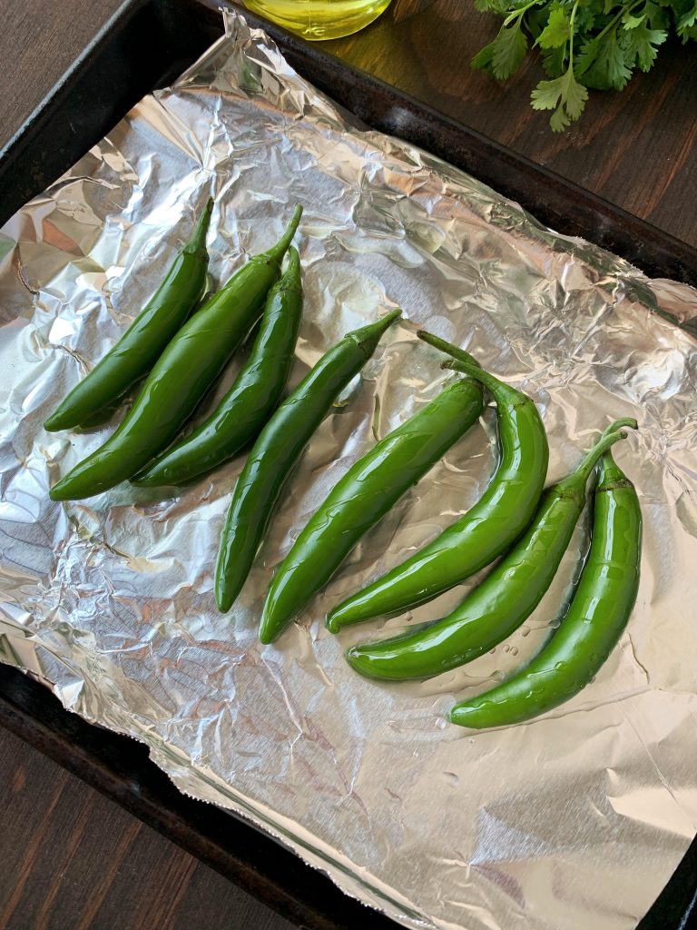 Serrano peppers on a baking sheet drizzled with olive oil