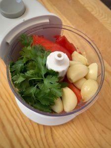 Garlic, cilantro, and tomatoes in mini food processor.