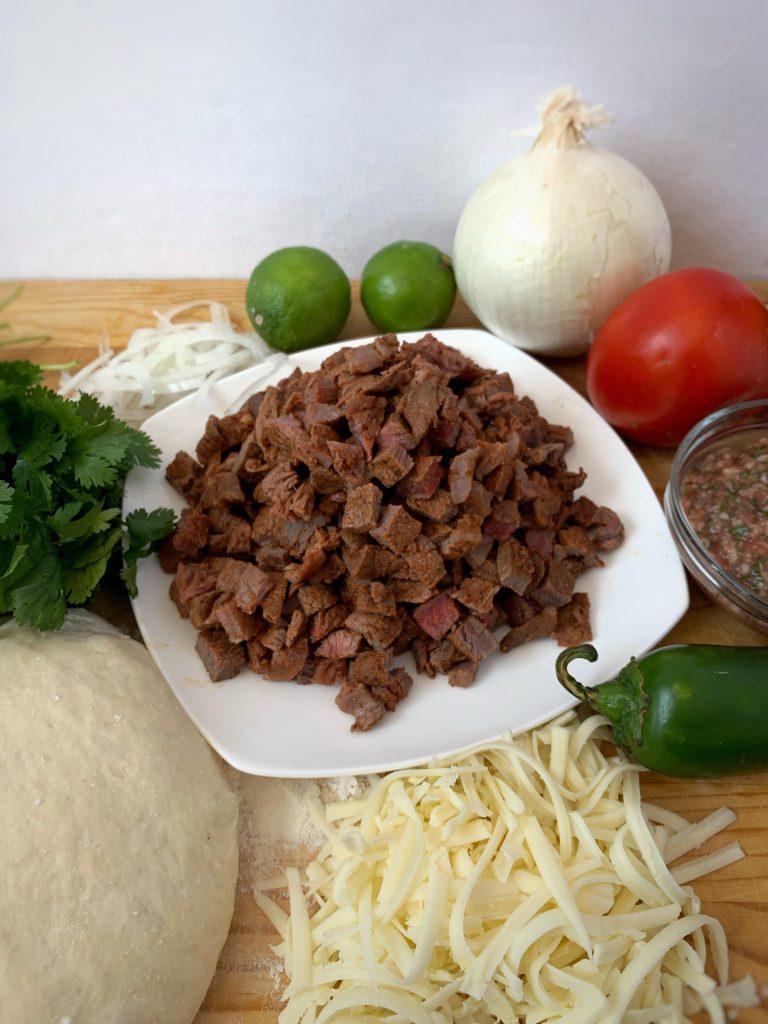 white onion, tomato, limes, jalapeno, cilantro, jack cheese, cotija cheese, pizza dough, and carne asada