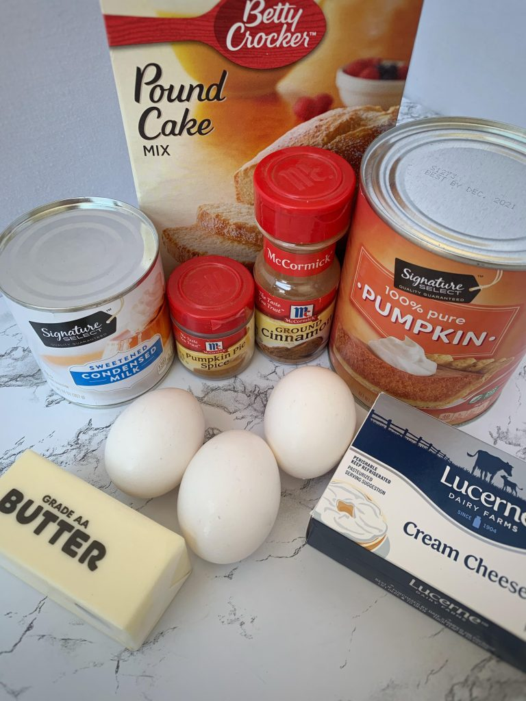 Pound cake mix, pumpkin, sweetened condensed milk, cinnamon, pumpkin pie spice, eggs, butter, and cream cheese on a counter