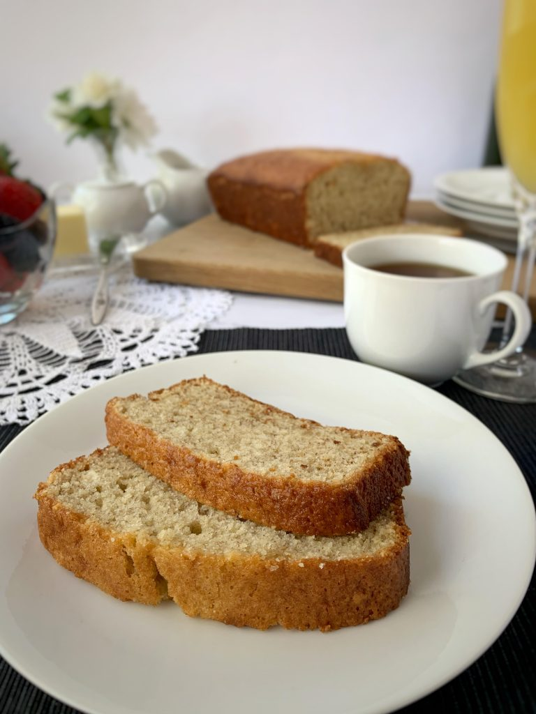 Slices of banana bread on a table set for brunch with coffee, berries, and flowers