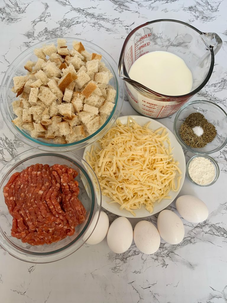 Ingredients for breakfast casserole- Cubed sourdough bread, milk, shredded fontina cheese, ground pork sausage, eggs, spices, and flour