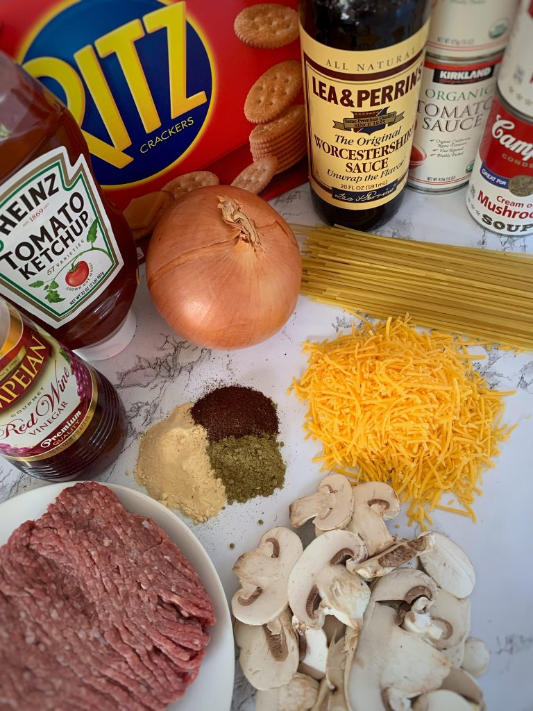 Ingredients for spaghetti casserole. Ground chuck, sharp cheddar cheese, spices, mushrooms, spaghetti noodles, onion, ketchup, ritz crackers, tomato sauce, cream of mushroom soup, red wine vinegar, Worcestershire