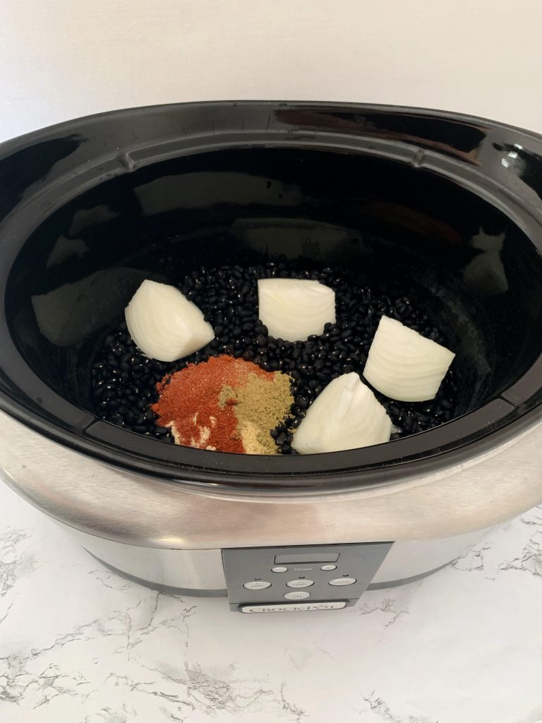 Black beans, onion, and spices in a Crockpot.