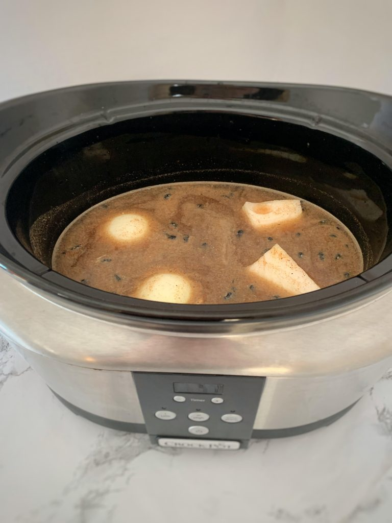Black beans, spices, and onion submerged in water in a slow cooker.