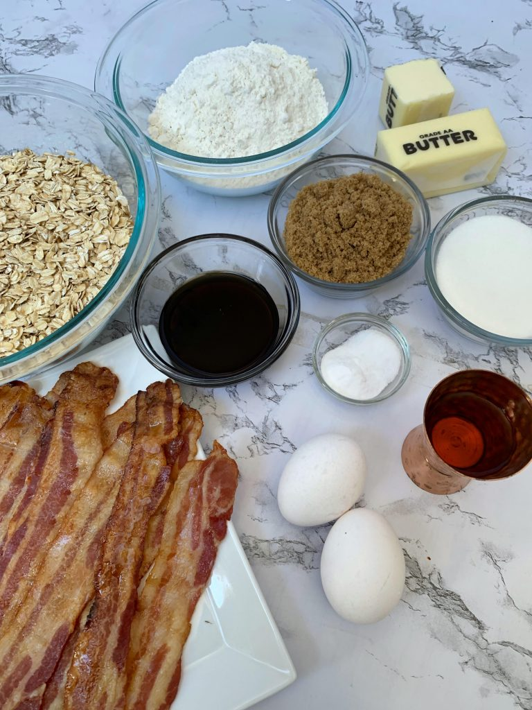 Ingredients for Whiskey Bacon Cookies. Bacon, eggs, whiskey, salt, flour, baking soda. brown sugar, white sugar, butter, maple syrup, and oats.