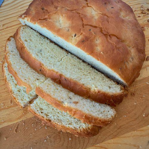 Fennel Bread loaf sliced on cutting board