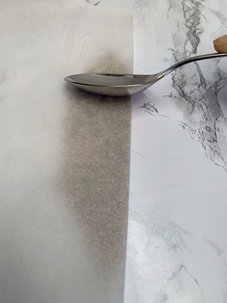 Spoon crushing fennel folding into parchment paper