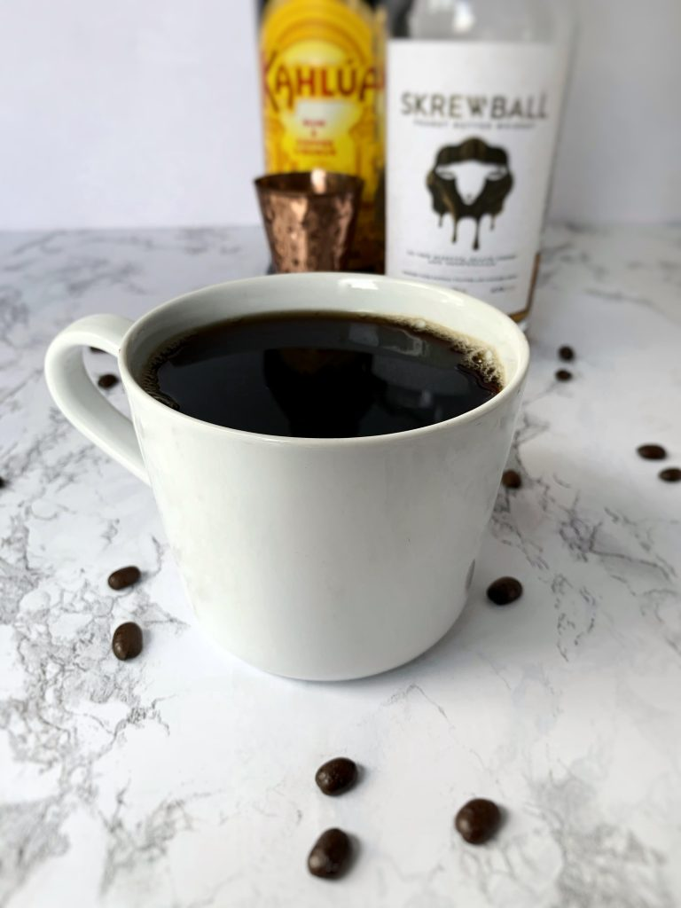 Coffee cup filled with Coffee, Kahlua, and Skrewball Peanut Butter Whiskey, surrounded by coffee beans and bottles of Skrewball and Kahlua