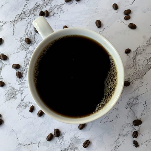 Coffee spiked with Skrewball Peanut Butter Whiskey and Kahlua coffee liqueur urrounded by coffee beans