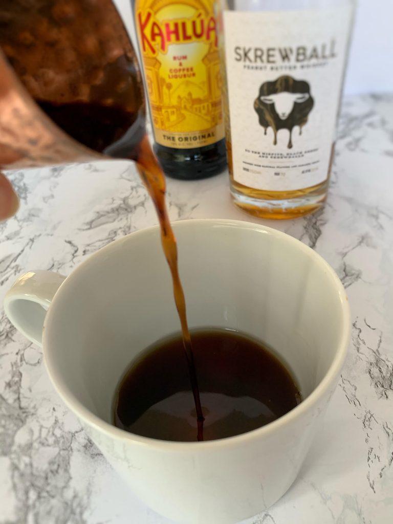 Pouring Kahlua Coffee Liqueur into coffee mug
