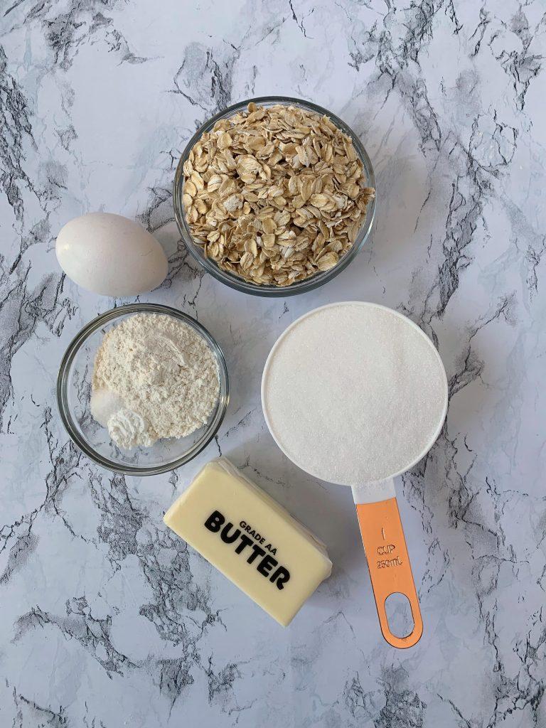 Ingredients for lace cookies; oats, butter, sugar, flour, salt, baking soda,. egg