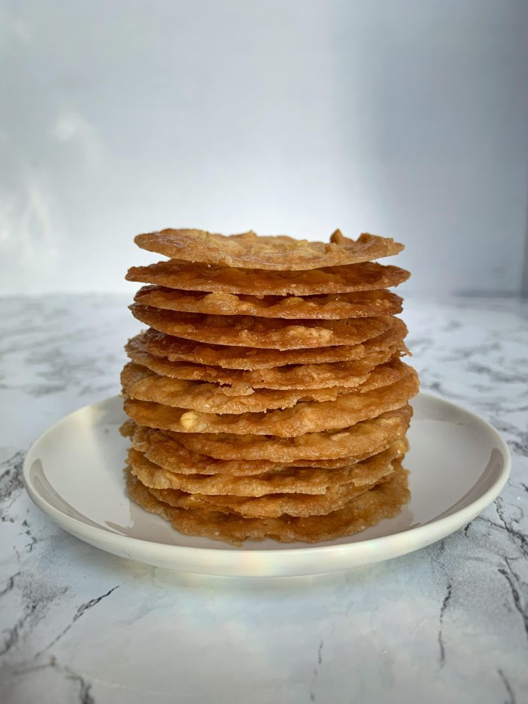 Lace cookies stacked on a white plate